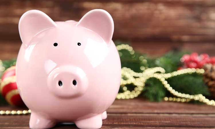 Smiling piggy bank with Christmas decor in the background