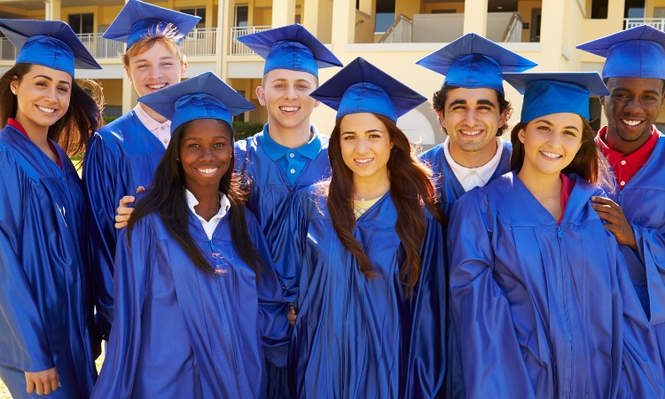 A group of young students in graduation cap and gowns.